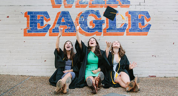 Graduates tossing caps into the air in front of War Eagle wall