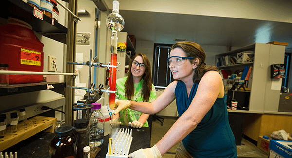 Women in protective eyewear performing experiment